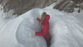 Woman is a tourist in the ice of Lake Baikal. A woman is a tourist and a traveler on the ice of Lake Baikal. The girl climbed up and stands in a small ice gorge stock footage