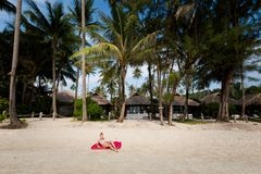 Woman tourist on Koh Kood. Summer landscape on tropical koh Kood island in Thailand. Young caucasian woman having sunbathon white sand beach with coconut palms Stock Image