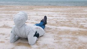 Woman tourist lies on a snowy sandy beach in winter by the sea. Woman in a jacket and jeans, back view. stock footage