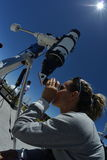 Woman tourist looking through big telescope Stock Photo