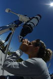 Woman tourist looking through big telescope Royalty Free Stock Image