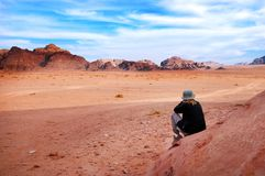 Woman tourist looks at the wonderful landscape view of Wadi Rum Jordan. A woman tourist looks at the wonderful landscape view of Wadi Rum, a protected desert royalty free stock images
