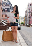 Woman tourist with luggage and map. Woman tourist standing in a street in a foreign town with her luggage and map which she is reading to find directions Stock Photo