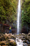Woman tourist and main waterfall at levada 25 fountains in Rabacal, Madeira island royalty free stock photo