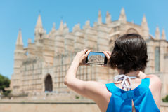 Woman tourist in Mallorca. Taking photographs of landmark buildings while enjoying the adventure of a a summer vacation in Europe, view from behind Stock Photos