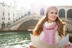 Woman tourist with map near Rialto Bridge looking into distance Royalty Free Stock Photo