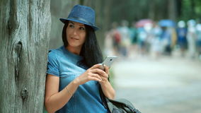Woman tourist with mobile phone texting sms in the park in warm spring day. stock video footage