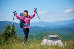 Woman tourist near camping in the mountains with backpack and trekking sticks in the morning stock photos