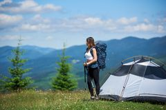 Woman tourist near camping in the mountains with backpack and trekking sticks in the morning. Slim girl climber with backpack and trekking sticks near tent on Royalty Free Stock Image