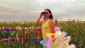 Woman tourist on the observation deck examines the sights with binoculars. The average plan stock video