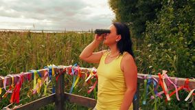 Woman tourist on the observation deck examines the sights with binoculars. The average plan stock video footage