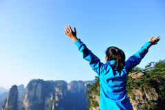 Woman tourist open arms at mountain peak zhangjiaj Royalty Free Stock Images