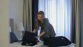 Woman tourist packing a suitcase in hotel stock footage