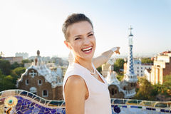 Woman tourist in Park Guell, Barcelona pointing on building Stock Photography