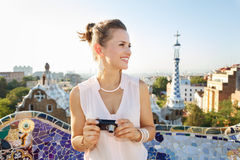 Woman tourist with photo camera looking aside in Park Guell. Refreshing promenade in unique Park Guell style in Barcelona, Spain. Happy young woman tourist Stock Photo
