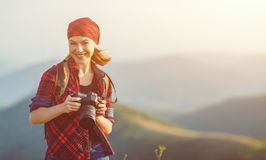 Woman tourist photographer with camera on top of mountain at sun Royalty Free Stock Images