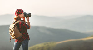 Woman tourist photographer with camera on top of mountain at sun Royalty Free Stock Photo