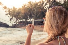 Woman tourist photographing beach sunset on smartphone during beach travel holidays stock image