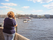 Woman tourist photographing the sights and sailing ships on the river in the summer. Saint-Petersburg. The River Neva. stock photo
