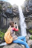 Woman on background of Svartifoss waterfall surrounded by basalt columns in the south of Iceland Stock Photography