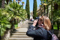 Woman tourist photographs attractions in park Stock Images