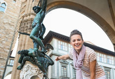 Woman tourist pointing on statue of Perseus, Florence, Italy. Its time to tick off must-see Florence treasures of a bucket list. Smiling young woman tourist Stock Photo