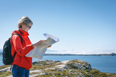 Woman tourist reading the map. During travel in Norway against blue hazy fjord background Royalty Free Stock Photography