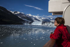 Woman tourist in red jacket on cruise ship. Admires scenery in College Fjord in Alaska Stock Image