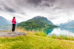 Woman tourist relaxing on fjord sea shore, Norway. Travel concept. Mature tourist woman on sea shore looking at fjords beautiful landscape, in Olden village Stock Image