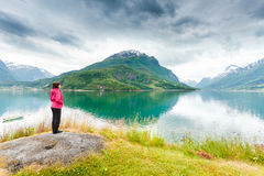 Woman tourist relaxing on fjord sea shore, Norway. Travel concept. Mature tourist woman on sea shore looking at fjords beautiful landscape, in Olden village Stock Photos