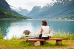 Woman tourist relaxing on fjord sea shore, Norway. Travel concept. Mature tourist woman sitting on bench on sea shore looking at fjords beautiful landscape, in Royalty Free Stock Photo