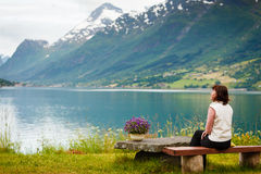 Woman tourist relaxing on fjord sea shore, Norway. Travel concept. Mature tourist woman sitting on bench on sea shore looking at fjords beautiful landscape, in Royalty Free Stock Photos