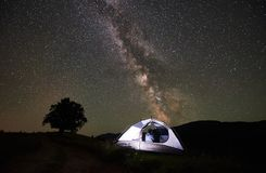 Woman tourist resting at night camping under starry sky and Milky way stock photo