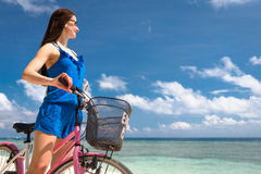Woman tourist riding bicycle at beach in vacation Royalty Free Stock Images