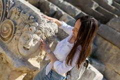 Woman tourist on the ruins of an ancient Roman city exploring and touching the ancient architecture in Demre, Turkey.  stock photo