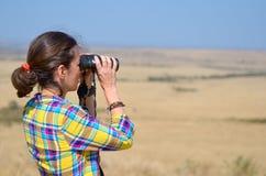 Woman tourist on safari in Africa, watching african savannah wildlife with binoculars Royalty Free Stock Photography
