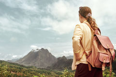 Woman tourist in shirt with backpack enjoying mountains view. Stock Photos