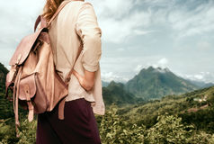 Woman tourist in shirt with backpack enjoying mountains view Stock Photography