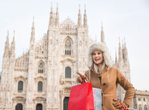 Woman tourist with shopping bags pointing on copy space in Milan Stock Images