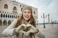 Woman tourist showing heart shaped hands on St. Marks Square Stock Photos