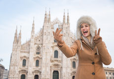 Woman tourist showing victory gesture and taking selfie in Milan Stock Photography