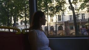 Woman tourist sightseeing through the tram window. Public transport in Europe. Woman tourist admiring the architecture traveling around the city by tram stock footage