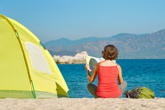 Woman tourist  sit near the tent looking the map Stock Images