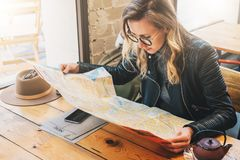 Woman tourist sits in cafe at table, looking for way on destination map. Girl rests in restaurant after sightseeing. Yung woman tourist in glasses sits in cafe Royalty Free Stock Images