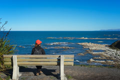 Woman tourist sitting on a bench enjoy ocean view Royalty Free Stock Photos