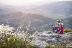 Woman tourist sitting on top of a mountain Stock Photography