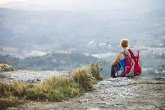 Woman tourist sitting on top of a mountain Royalty Free Stock Images