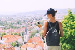 Woman with smartphone in hand on background of Ljubljana City, S. Woman tourist with smartphone in hand on background of panoramic view with red roofs of royalty free stock photo