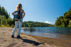 Woman tourist stands on the coast. Of the lake and enjoying view of the lake and volcano on the horizon stock photography