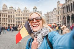 Woman tourist stands with the flag of Belgium on the background of the Grand-Place or the Grand Market Square in royalty free stock photos
